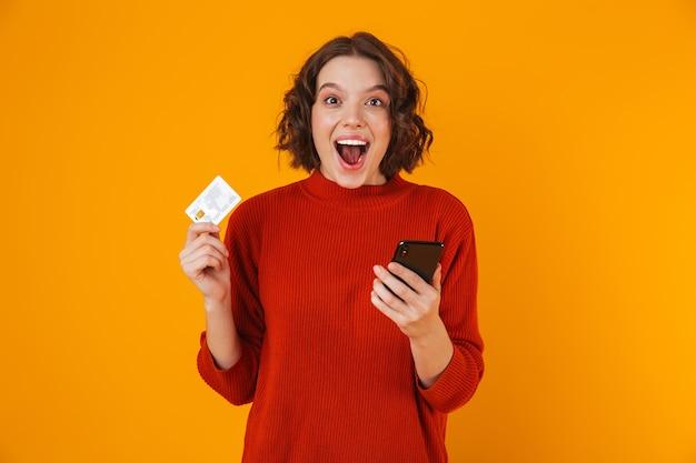 Portret emocjonalnej kobiety 20s na sobie sweter za pomocą telefonu komórkowego i karty kredytowej, stojąc na białym tle nad żółtym