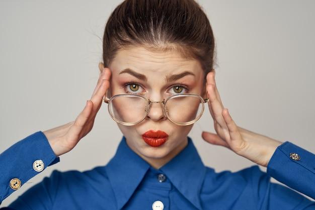 Portret emocjonalnej kobiety w niebieskiej koszuli i okularach jasny makijaż modelu jasnym tle przycięty widok copy space. wysokiej jakości zdjęcie