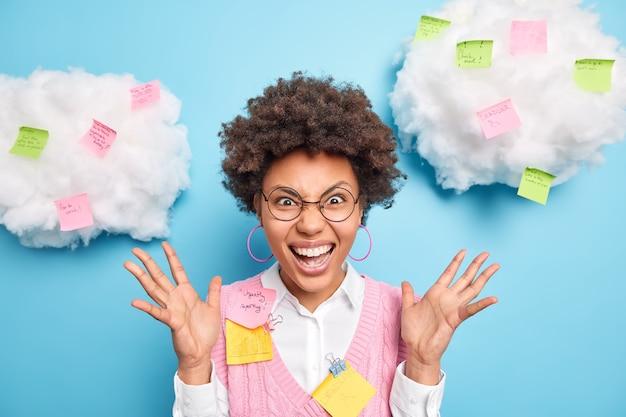 Portret emocjonalnej pracowniczki biurowej unosi dłonie i krzyczy gniewnie na stażystę ma termin, który ma wiele do zrobienia, otoczony notatkami przypominającymi przyklejonymi do białych chmur
