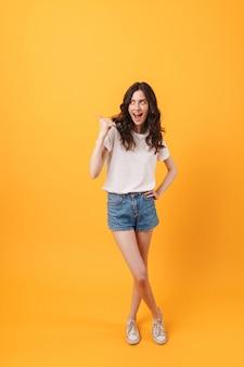Portret emocjonalnej szczęśliwej młodej kobiety pozuje na białym tle nad żółtą ścianą, wskazując na copyspace