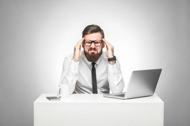 Portret emocjonalnie zdenerwowanego młodego menedżera w białej koszuli i czarnym krawacie siedzi w biurze i krzywiąc się, popełnił duży błąd ze zestresowaną twarzą, trzymając palce w pobliżu skroni. zdjęcia studyjne