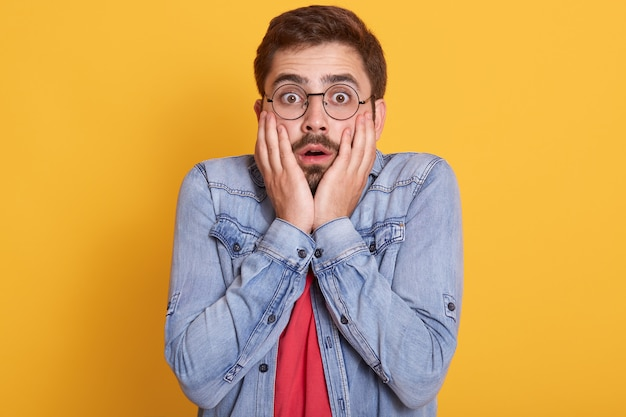 Portret emocjonalnie zszokowanego przestraszonego faceta, który szeroko otwiera oczy i usta, kładąc dłonie na twarzy, pod wrażeniem wyrazu twarzy