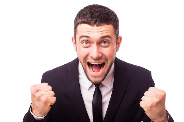 Portret energicznego młodego biznesmena, cieszącego się sukcesem, krzycząc przed białym - na białym tle