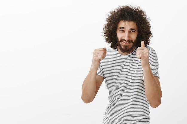 Portret energicznego, przystojnego faceta ze wschodu z kręconymi fryzurami i brodą, unoszący zaciśnięte pięści i uśmiechający się z niecierpliwym wyrazem twarzy