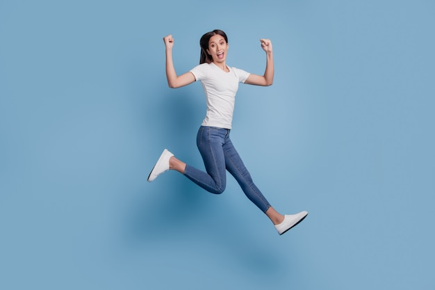 Portret energicznej beztroskiej podekscytowanej pani skok zwycięzca koncepcji na niebieskim tle