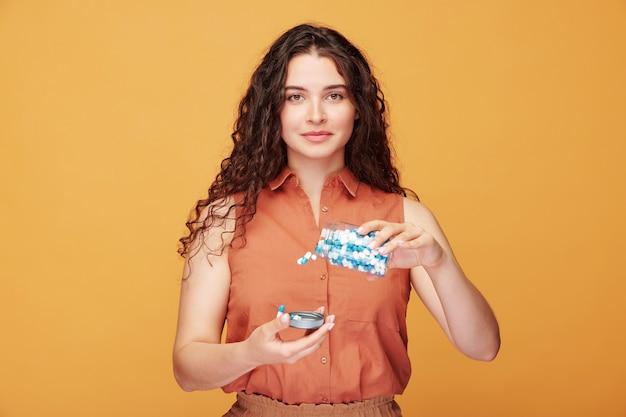 Portret energicznej dziewczyny z kręconymi włosami w koszuli bez rękawów, wlewającej tabletki w osłonę na pomarańczowo
