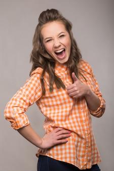 Portret energicznej zabawy ucznia dziewczyny na szarym tle w dżinsowej kurtce