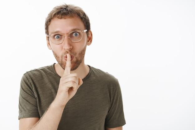 Portret entuzjastycznego, zabawnego i radosnego, atrakcyjnego dorosłego mężczyzny ze składanymi ustami z włosia w dźwięku shhh, trzymającego palec wskazujący nad ustami podczas uciszania, aby zachować tajemnicę