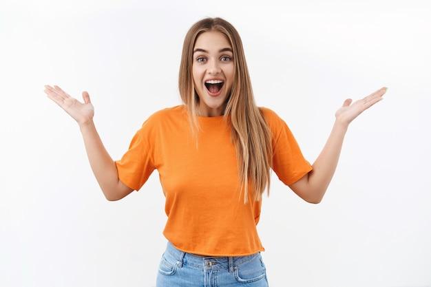 Portret entuzjastycznej blond dziewczyny wyraża radość i zaskoczenie, rozkłada ręce na boki i uśmiecha się rozbawiony, słyszy niesamowite informacje, reaguje na szczęśliwą niesamowitą sytuację