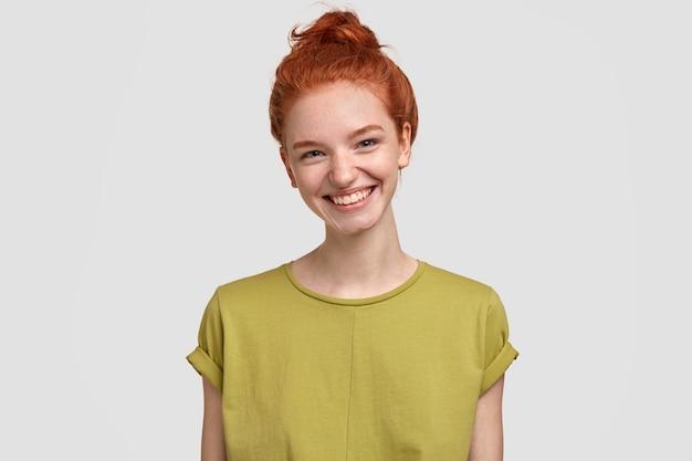 Portret entuzjastycznej rudej dziewczyny z węzłem, szeroko się uśmiecha, radośnie śmieje się z zabawnych plotek, nosi zwykłą zieloną koszulkę, modelki na białej ścianie. student treści ma przerwę po zajęciach w sali