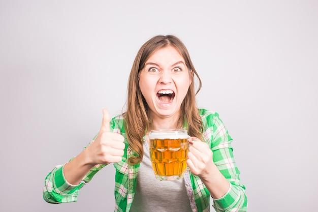 Portret euforyczny miłośnik sportu, trzymając butelkę piwa. kobieta z piwem.