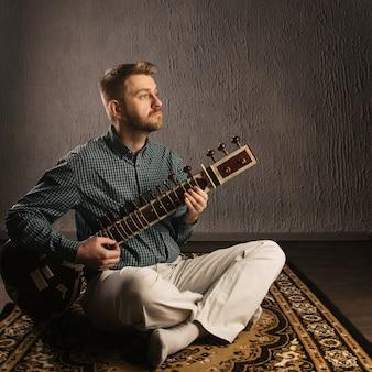Portret europejczyka grającego na sitarze, siedzącego na dywanie - obraz