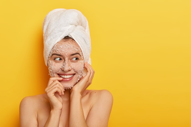 Portret europejki stosuje organiczną maseczkę do oczyszczania skóry, dba o cerę, uśmiecha się delikatnie, pokazuje białe zęby, ma odsłonięte ramiona, stoi na żółtej ścianie z pustą przestrzenią
