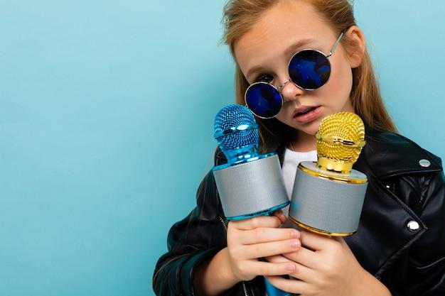 Portret europejska dziewczyna w okularach przeciwsłonecznych z dwa mikrofonami w rękach na bławym