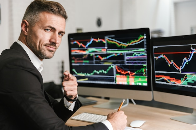 Portret europejskiego biznesmen 30s na sobie garnitur siedzi w biurze i pracy z grafiką cyfrową na komputerze
