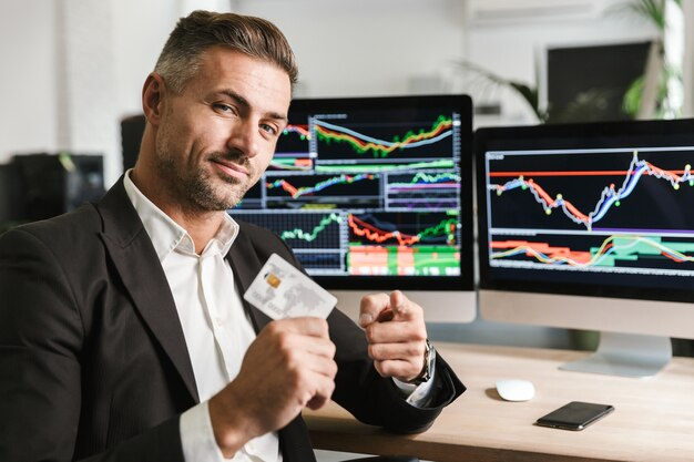 Portret europejskiego biznesmena lat 30. ubrany w garnitur trzyma kartę kredytową siedząc w biurze i pracując z cyfrową grafiką na komputerze