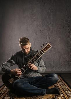 Portret europejskiego mężczyzny grającego na sitarze, siedzącego na dywanie