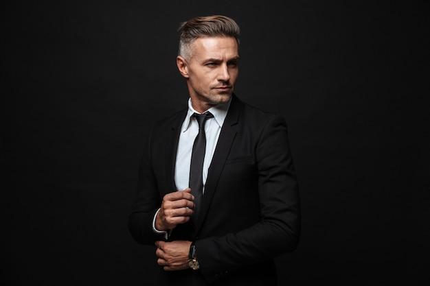 Portret europejskiego przystojnego biznesmena ubranego w formalny garnitur pozowanie i odwrócenie wzroku na białym tle nad czarną ścianą
