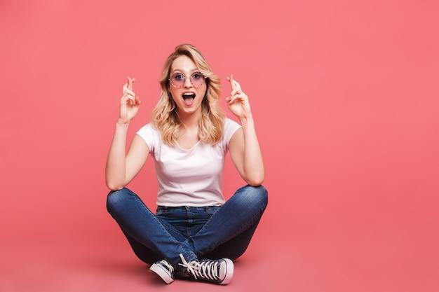 Portret europejskiej blond kobiety noszącej okulary przeciwsłoneczne w stylu vintage, śmiejąc się siedząc na podłodze ze skrzyżowanymi nogami izolowanymi na różowej ścianie