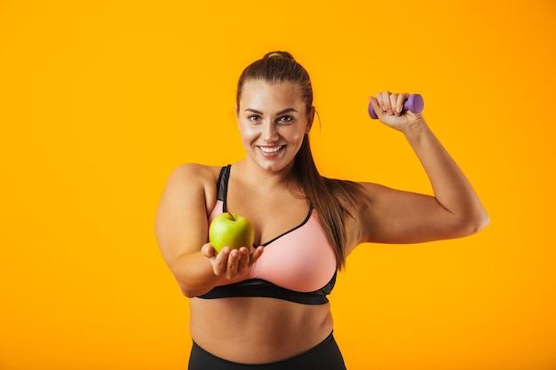 Portret europejskiej grube kobiety w stanik sportowy trzymając jabłko i podnoszenia hantle, na białym tle nad żółtym tle
