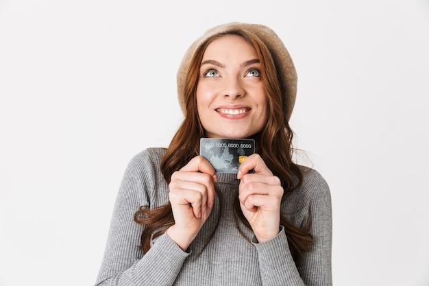 Portret europejskiej kobiety w wieku 30 lat w kapeluszu uśmiechniętej i trzymającej kartę kredytową na białym tle