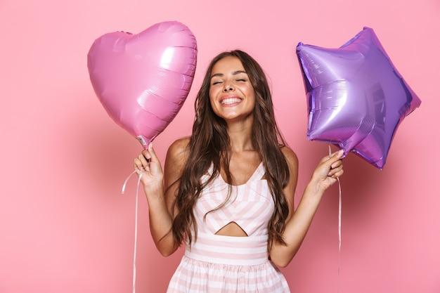 Portret europejskiej ładnej dziewczyny 20s z długimi włosami na sobie sukienkę, uśmiechając się i trzymając dwa balony, odizolowane na różowej ścianie
