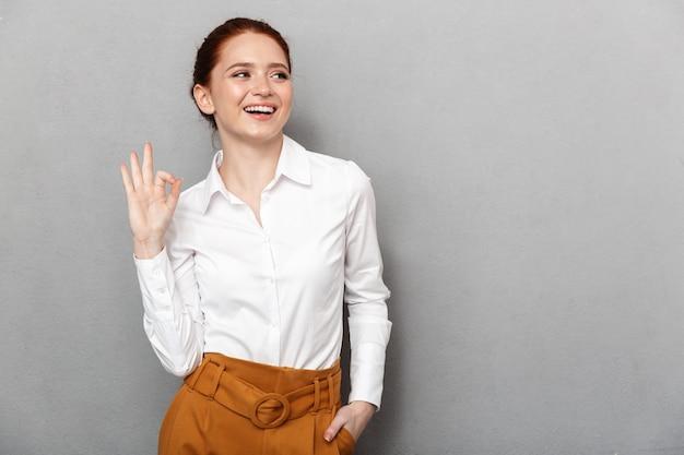 Portret europejskiej rudowłosej bizneswoman 20s w formalnym stroju, uśmiechniętej i pokazującej ok znak w biurze na białym tle nad szarym