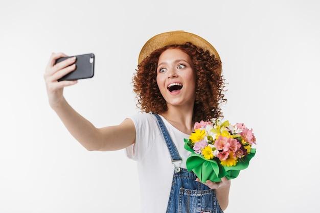 Portret europejskiej rudowłosej kręconej kobiety lat 20. w letnim słomkowym kapeluszu robi zdjęcie selfie, trzymając pudełko na kwiaty na białym tle nad białą ścianą