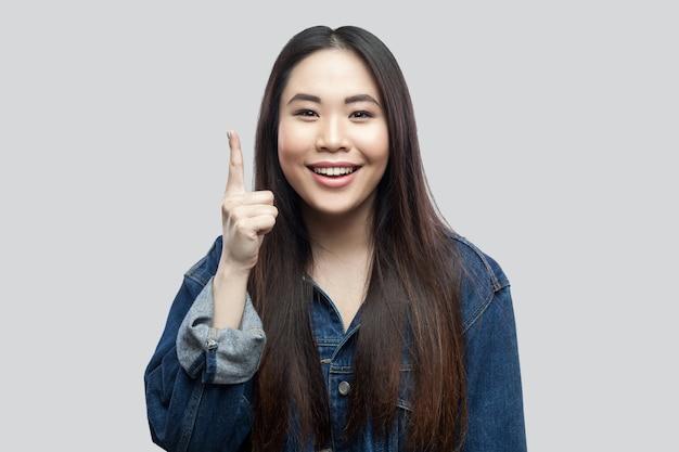 Portret exicted piękna brunetka azjatyckie dziewczyny w niebieskiej kurtce dżinsowej, makijaż stojąc i patrząc na kamery z uśmiechem toothy, palec w górę. kryty strzał studio, na białym tle na jasnoszarym tle.