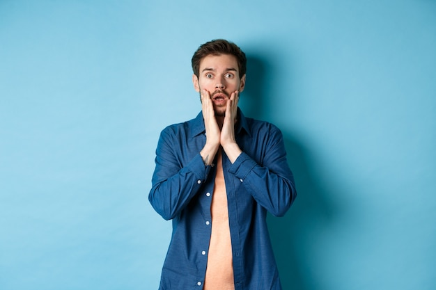 Portret faceta sapiącego i opadającej szczęki ze zszokowaną twarzą, wpatrującego się w kamerę zaskoczony, stojącego na niebieskim tle.