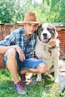 Portret faceta w kapeluszu, przytulającego psa w wiosce