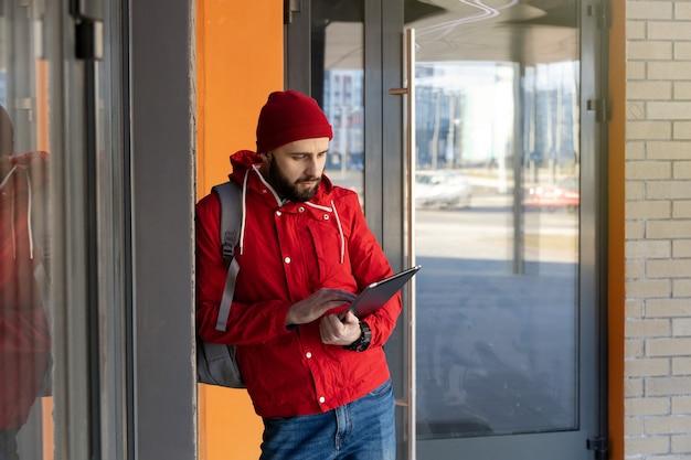 Portret faceta z brodą w czerwonej kurtce i dżinsach, który pozuje przy ścianie z tabletem
