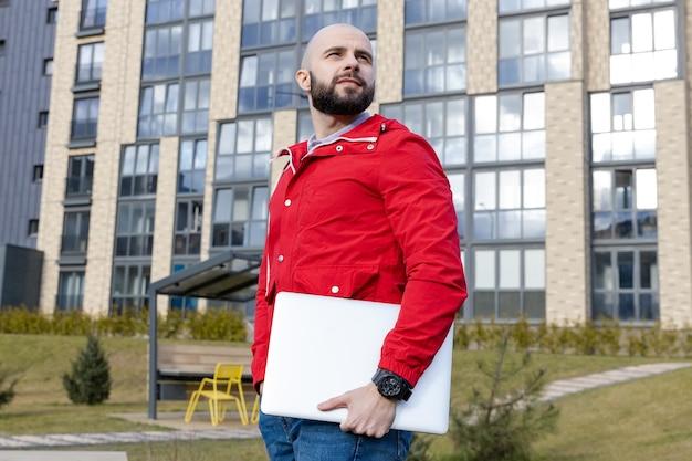 Portret faceta z brodą w czerwonej kurtce i dżinsach trzymającego laptopa na tle bloku miasta. pojęcie pracy na zlecenie
