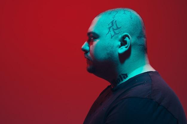 Portret faceta z kolorowym neonem na czerwonej ścianie. model męski o spokojnym i poważnym nastroju. wyraz twarzy, styl życia i wygląd millenialsów. przyszłość, technologie.