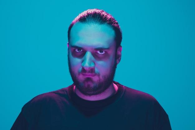 Portret faceta z kolorowym neonowym światłem na niebieskiej ścianie. model męski o spokojnym i poważnym nastroju. wyraz twarzy, styl życia i wygląd millenialsów. przyszłość, technologie.
