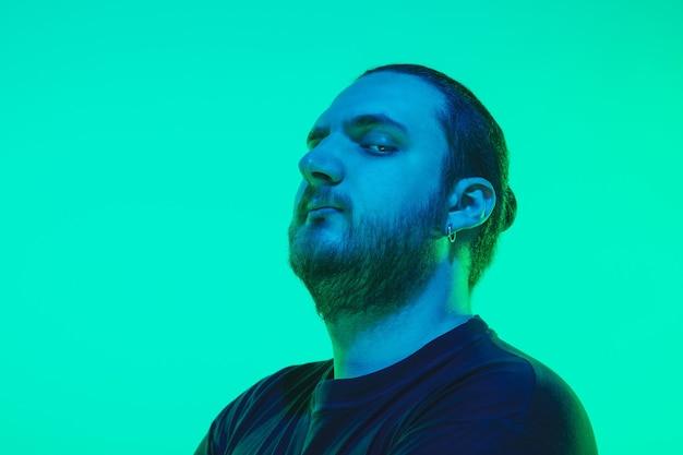 Portret faceta z kolorowym neonowym światłem na zielonej ścianie. model męski o spokojnym i poważnym nastroju. wyraz twarzy, styl życia i wygląd millenialsów. przyszłość, technologie.