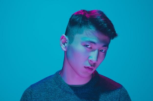 Portret faceta z kolorowym światłem neonowym na niebieskim tle studia. model męski o spokojnym i poważnym nastroju. wyraz twarzy, cyberpunk, styl życia i wygląd millenialsów. przyszłość, technologie.