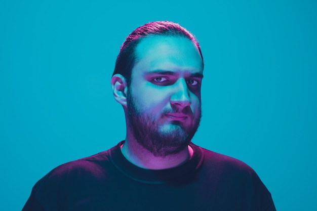 Portret faceta z kolorowym światłem neonowym na niebieskim tle studia. model męski o spokojnym i poważnym nastroju.