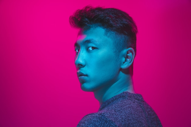 Portret faceta z kolorowym światłem neonowym na różowym tle studio. model męski o spokojnym i poważnym nastroju. wyraz twarzy, cyberpunk, styl życia i wygląd millenialsów. przyszłość, technologie.
