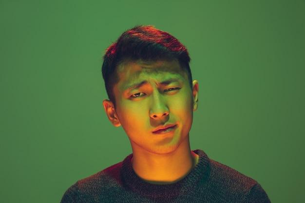 Portret faceta z kolorowym światłem neonowym na zielonym tle studia. model męski o spokojnym i poważnym nastroju. wyraz twarzy, cyberpunk, styl życia i wygląd millenialsów. przyszłość, technologie.