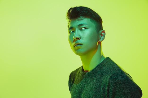 Portret faceta z kolorowym światłem neonowym na żółtym tle studia. model męski o spokojnym i poważnym nastroju. wyraz twarzy, cyberpunk, styl życia i wygląd millenialsów. przyszłość, technologie.