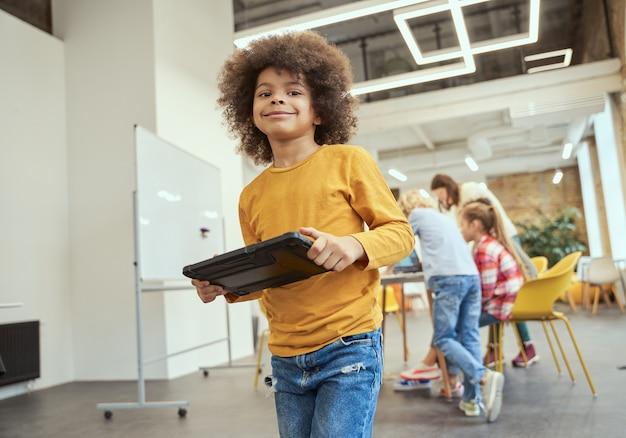 Portret fajnego chłopca uśmiechającego się do kamery trzymającej komputer typu tablet stojący w klasie podczas łodygi