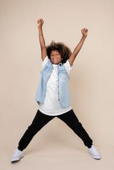 Portret fajnego nastoletniego chłopca podnoszącego ręce do góry