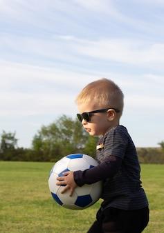 Portret fajny maluch dziecko w okulary stojący w trawie pole stepping jedną nogę na piłkę nożną. stylowy mały piłkarz na placu zabaw lub w parku. koncepcja aktywnego dzieciństwa i sportu dla dzieci
