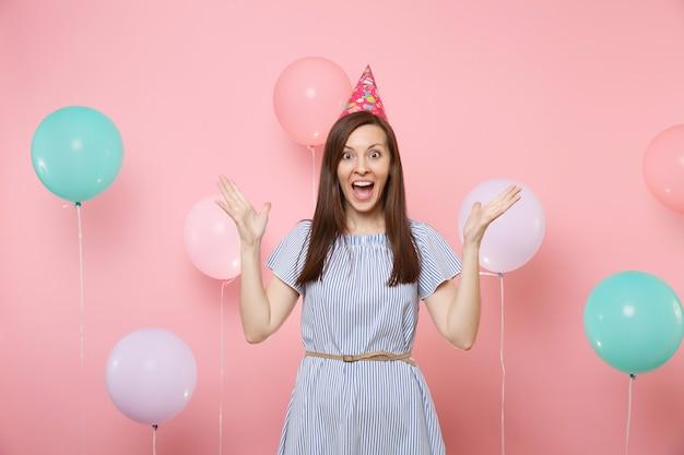 Portret fascynującej młodej kobiety szczęśliwej w urodzinowym kapeluszu i niebieskiej sukience rozkładając ręce na jasnym modnym różowym tle z kolorowymi balonami. urodziny wakacje, ludzie szczere emocje.
