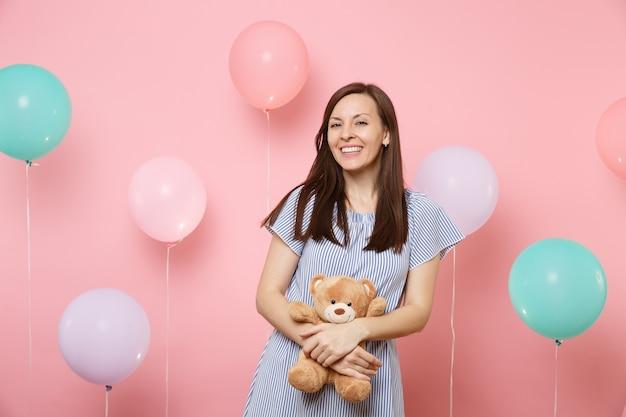 Portret fascynującej radosnej młodej kobiety w niebieskiej sukience, trzymając i przytulając pluszowego misia na różowym tle z kolorowymi balonami. urodziny wakacje party ludzie szczere emocje koncepcja.