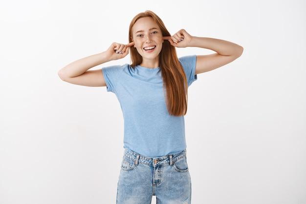 Portret figlarnej beztroskiej i optymistycznej uroczej rudowłosej suczki z piegami zamykającymi uszy palcami wskazującymi i uśmiechającej się z radości, unikając kłótni