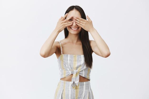 Portret figlarnej, szczęśliwej atrakcyjnej dziewczyny w dopasowanych ubraniach, zakrywającej oczy dłońmi i radośnie zerkającej przez palce, pozując na szarej ścianie