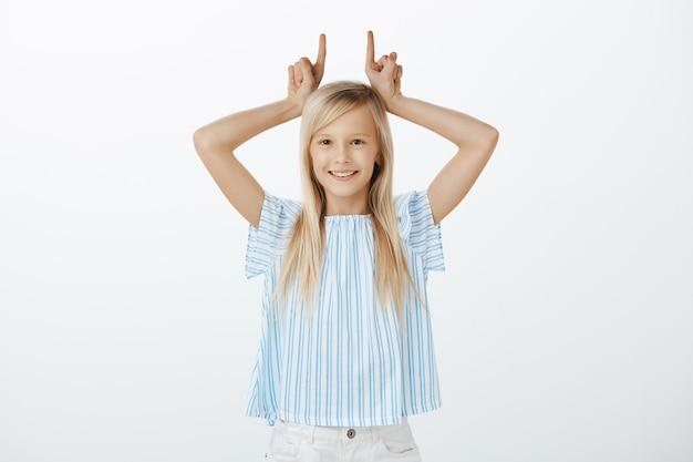 Portret figlarnej uroczej dziewczynki o blond włosach, bawiącej się kpiąco, trzymającej palce wskazujące nad głową, jakby pokazywała rogi, uśmiechającej się radośnie nad szarą ścianą