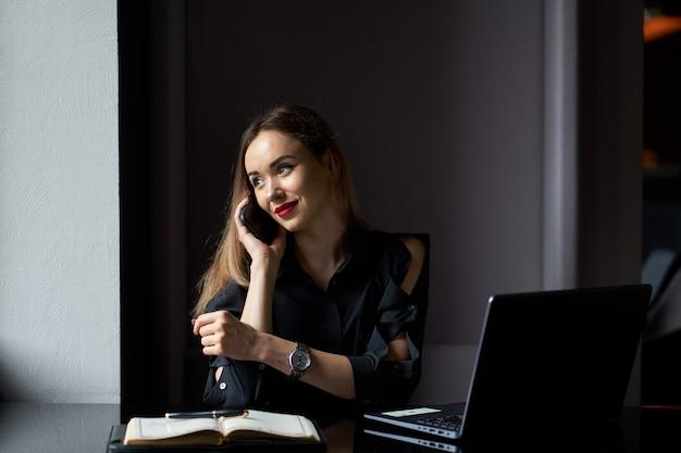 Portret firmy. piękna modna pozytywna biznesowa kobieta z laptopem i dzienniczkiem siedzi na miejscu pracy i rozmawia przez telefon.